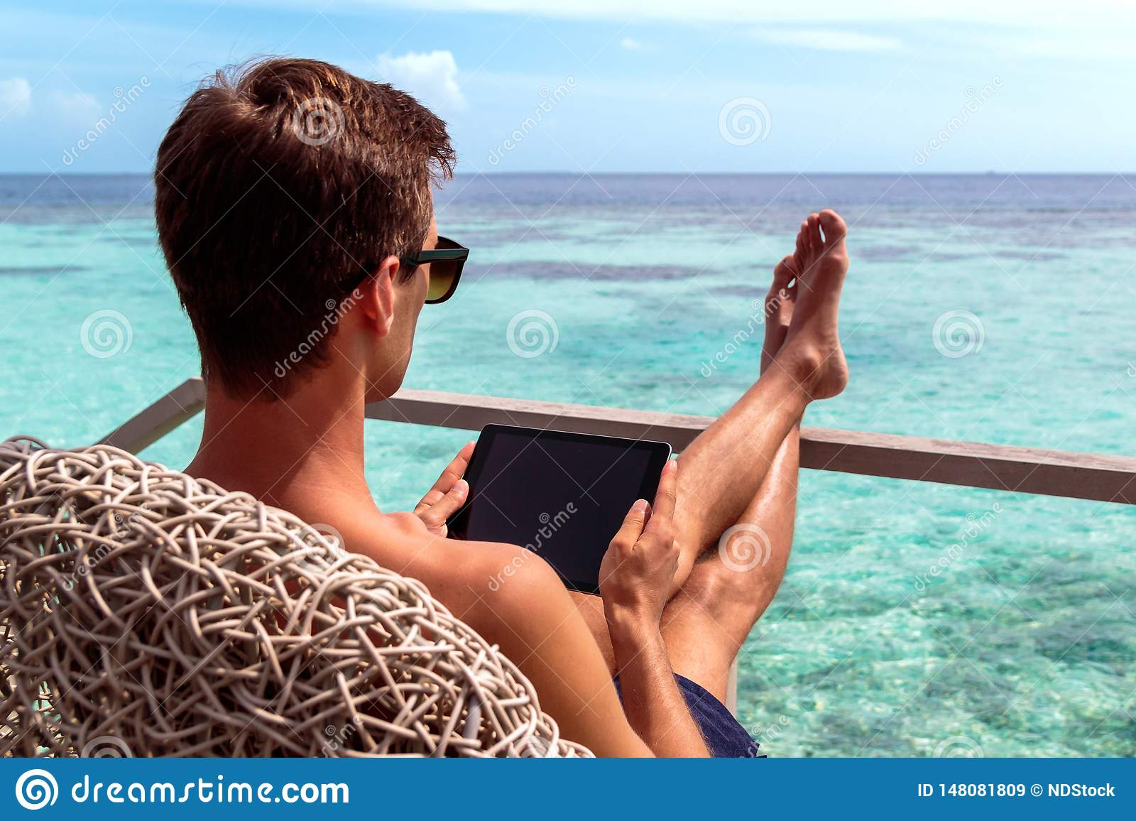 Young man in swimsuit working on a tablet in a tropical destination