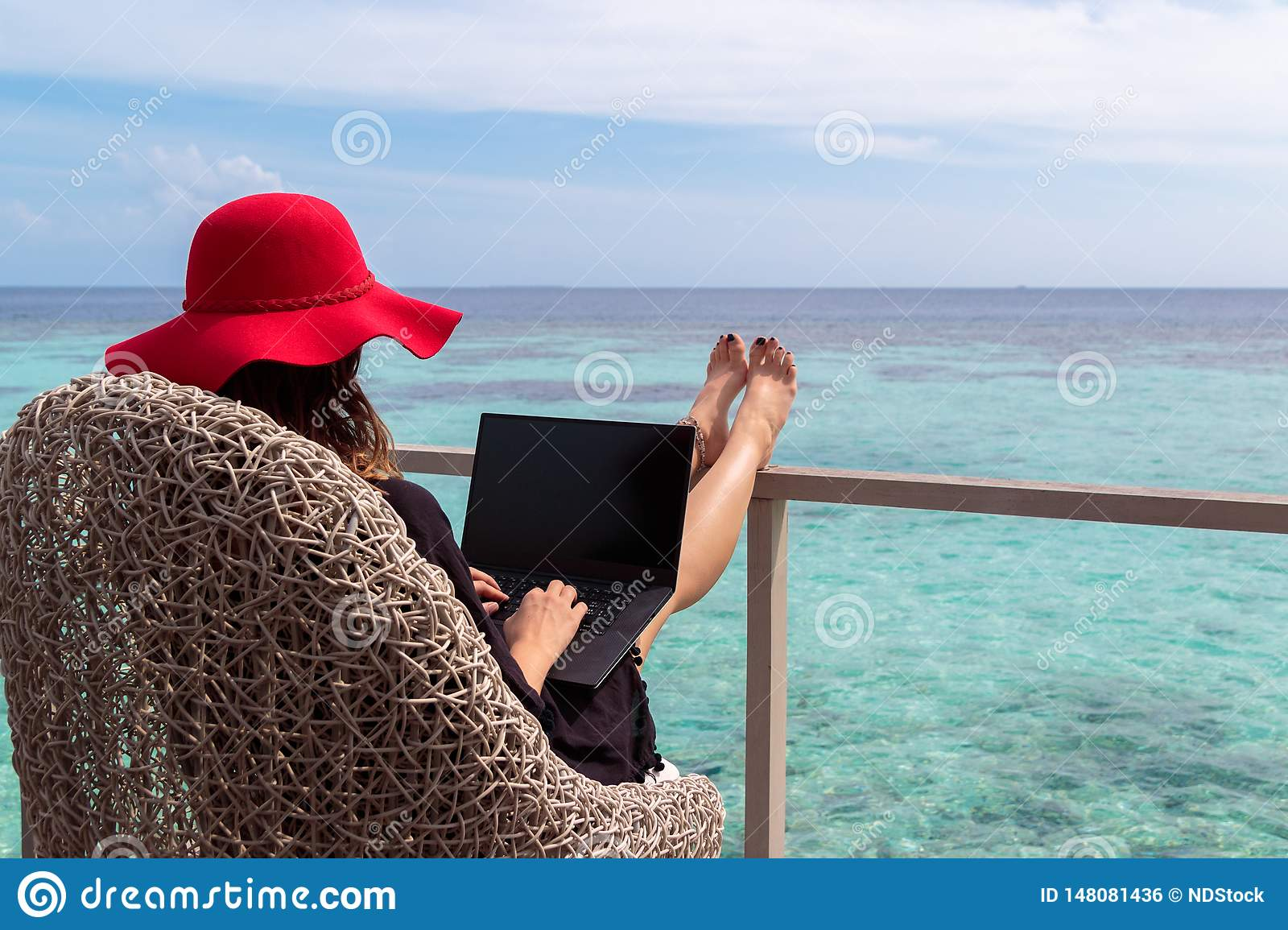 Young woman with red hat working on a computer in a tropical destination