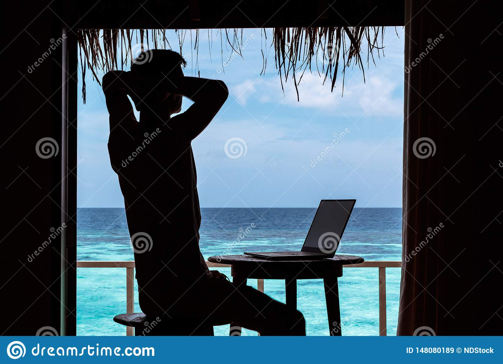 Silhouette of a young man relaxing while working with a computer on a table. Clear blue tropical water as background