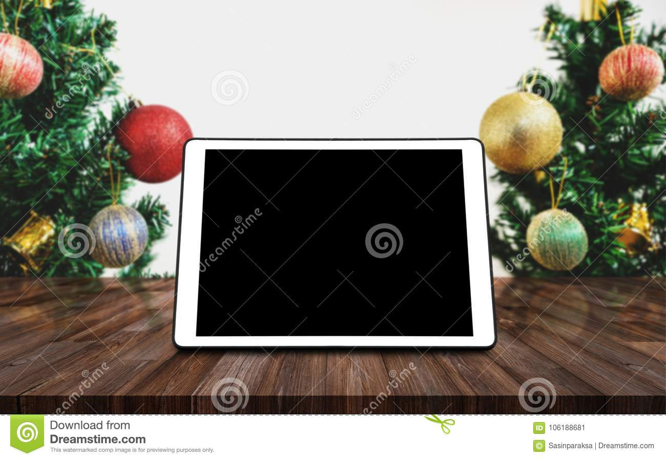 digital tablet blank black screen on wooden desk with christmas tree and decorations background - Christmas Digital Decorations