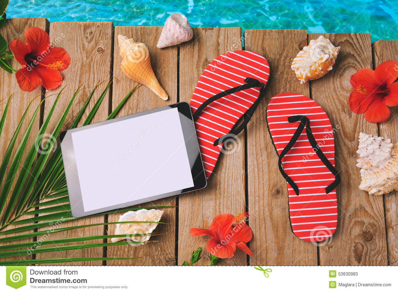 Digital tablet, flip flops and hibiscus flowers on wooden background. Summer holiday vacation concept. View from above