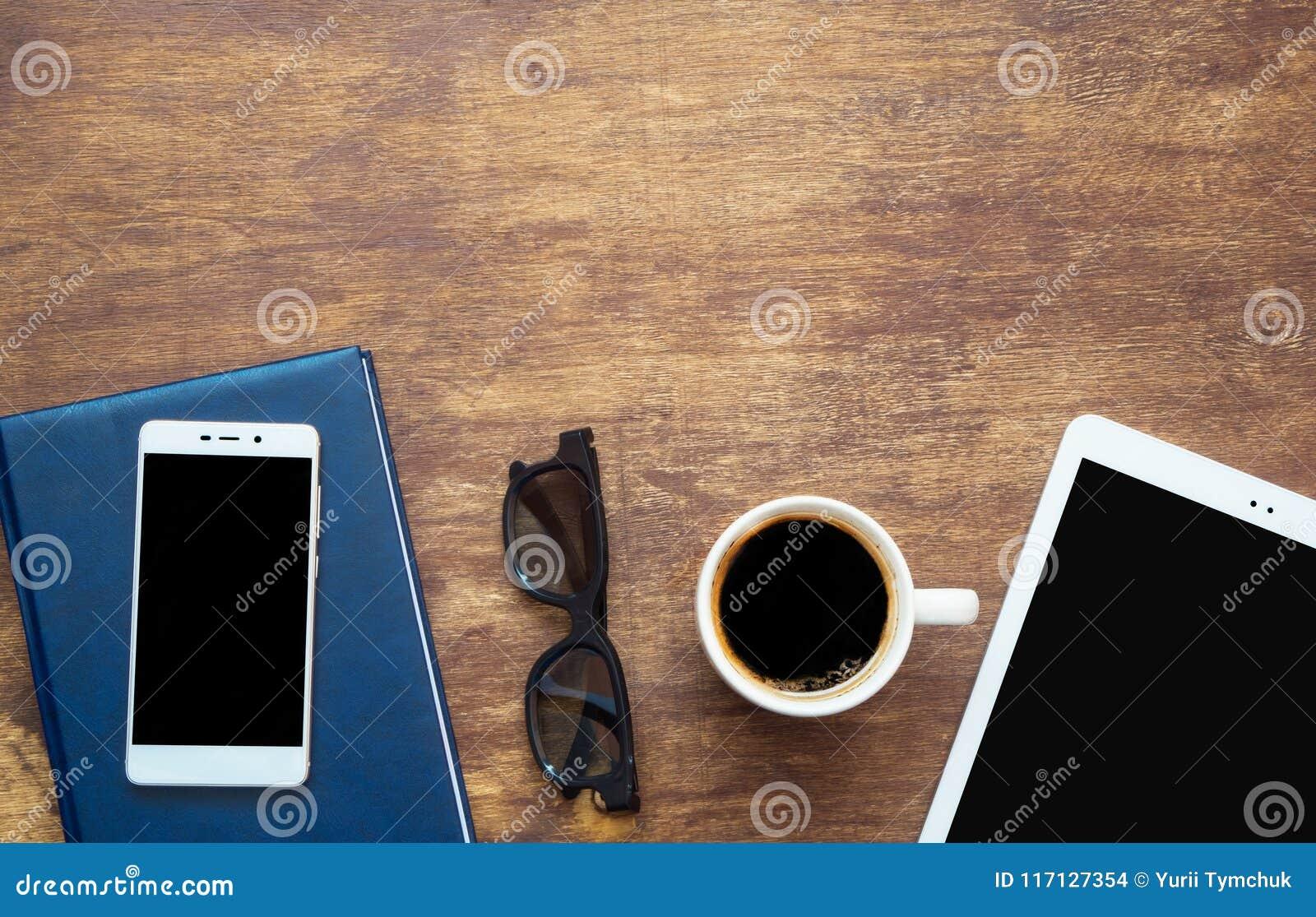 Digital-Tablette und -Tasse Kaffee auf hölzernem Schreibtisch Intelligentes Telefon auf Th
