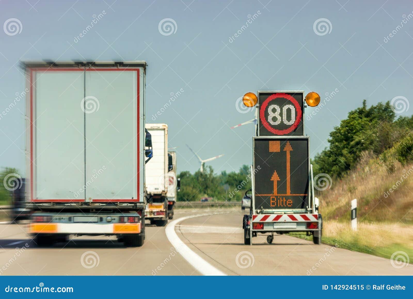 Digital trafiktecken som indikerar en motorwaykonstruktionsplats med det tyska ordet för 'pleases i skärmen