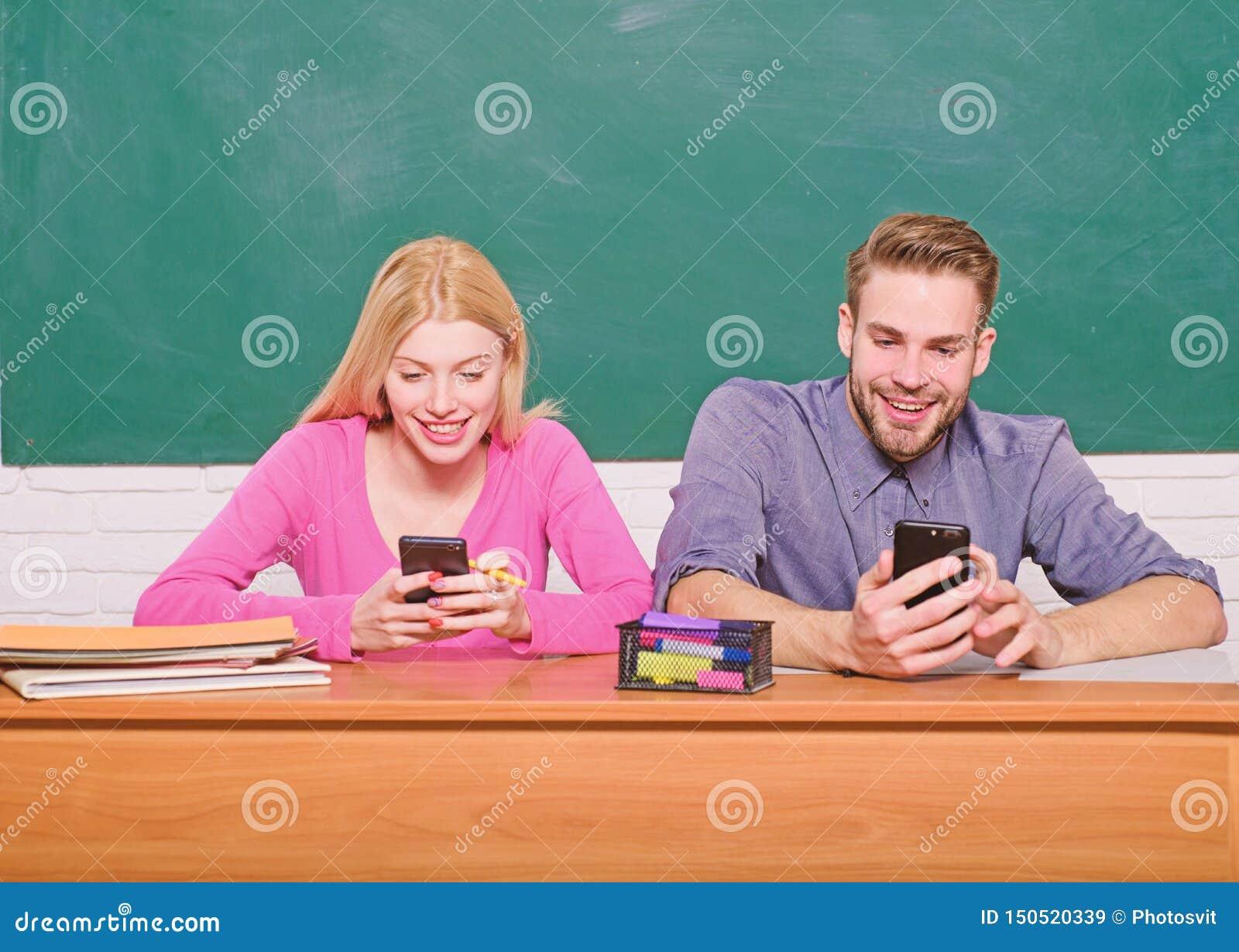 Digital v?rld Hem- skolg?ng Par av mannen och kvinnan i klassrum tillbaka skola till modern skola Deltagaren av den h?ga gruppen