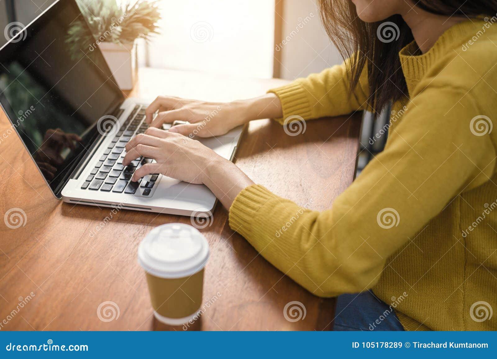Digitale levensstijl die buiten bureau werken De vrouw overhandigt het typen laptop computer met het lege scherm op lijst in koff