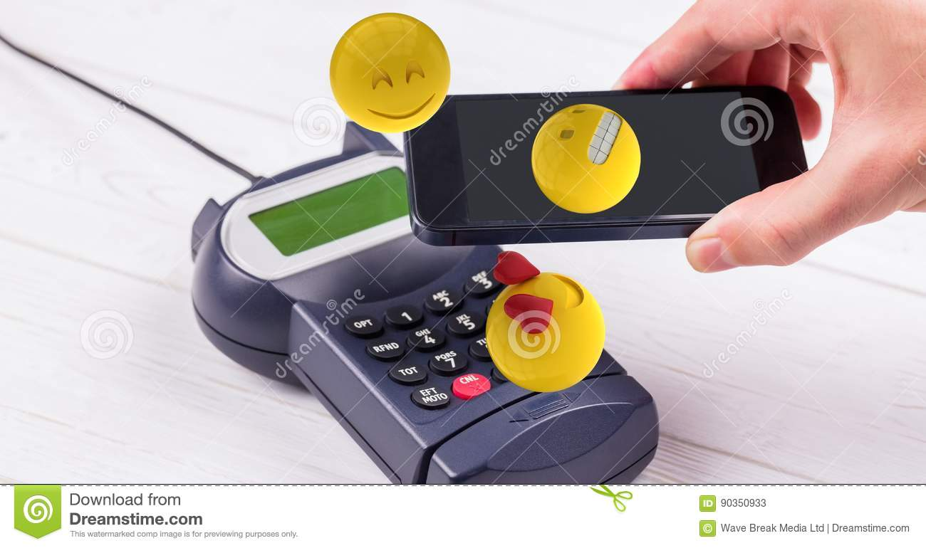 Digitally generated image of hand holding smart phone over credit card reader with emojis
