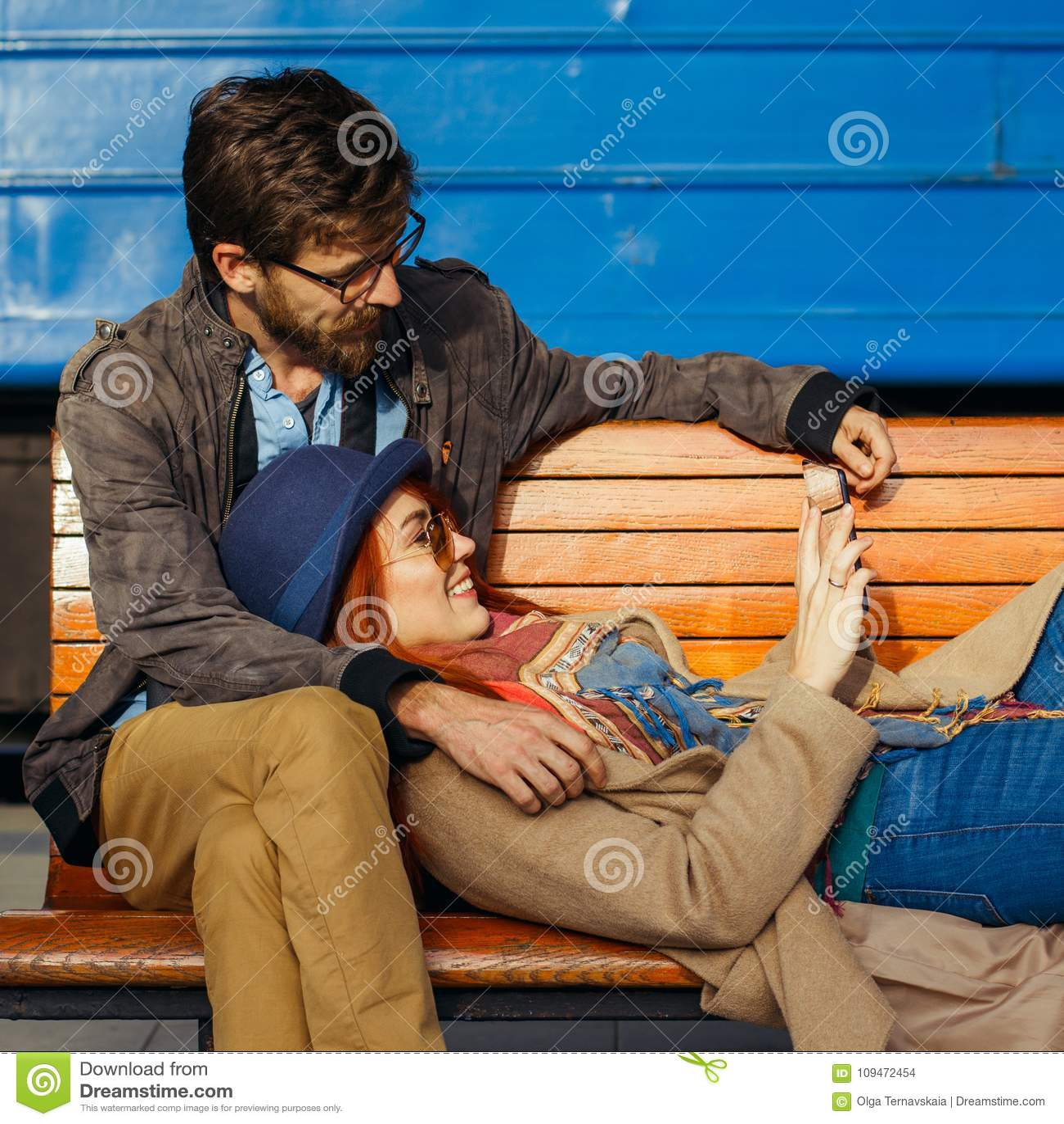 Digitaltechnik und Reisen Junge liebevolle Paare im Hippie tragen mit Tablet-Computer beim Sitzen im Bahnstation wai