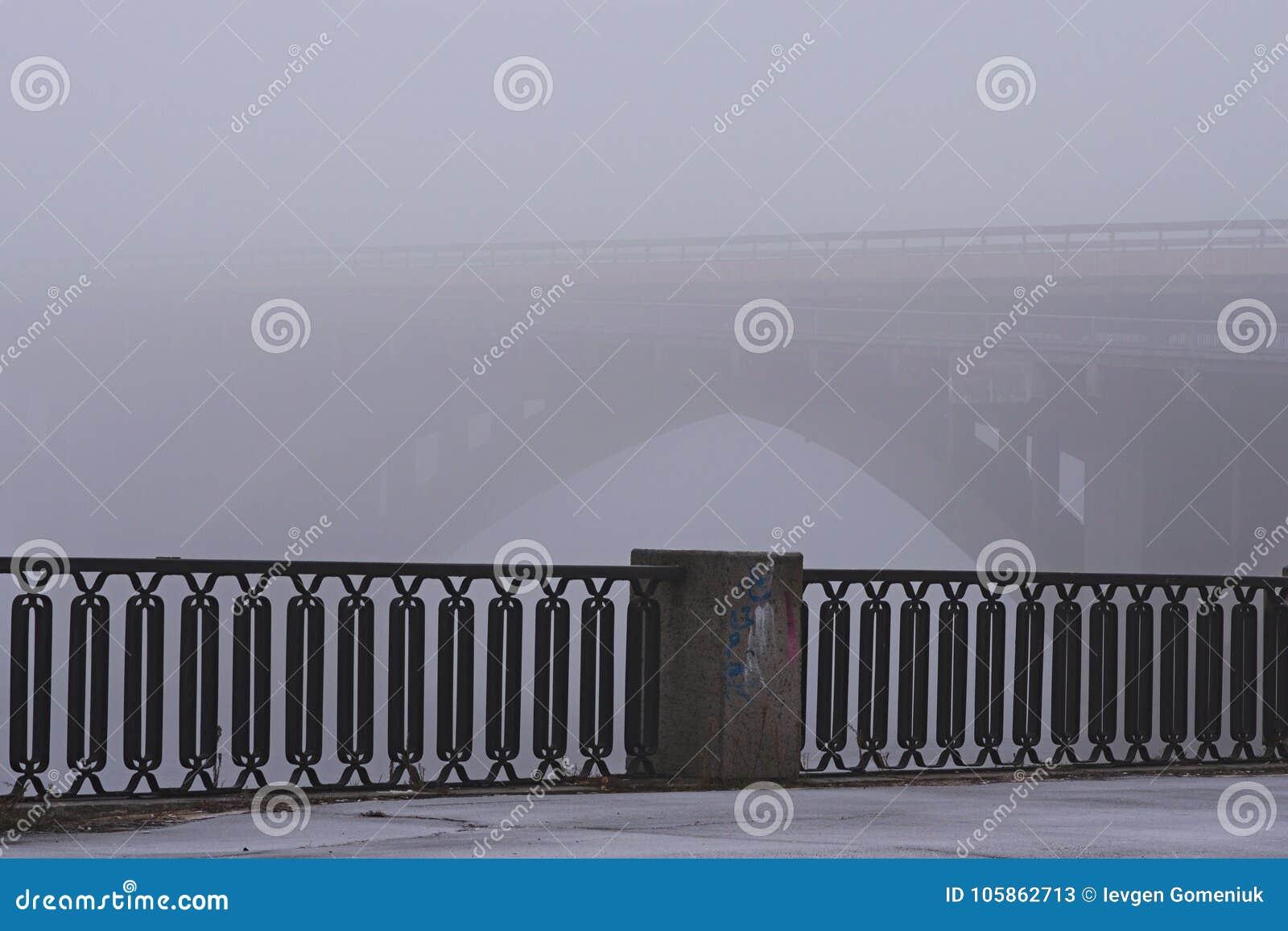 Dijk langs de Dnieper-rivier Steenmetro metrobrug in rijke mist, mistachtergrond De mening van de de winterochtend Kyiv, de Oekra