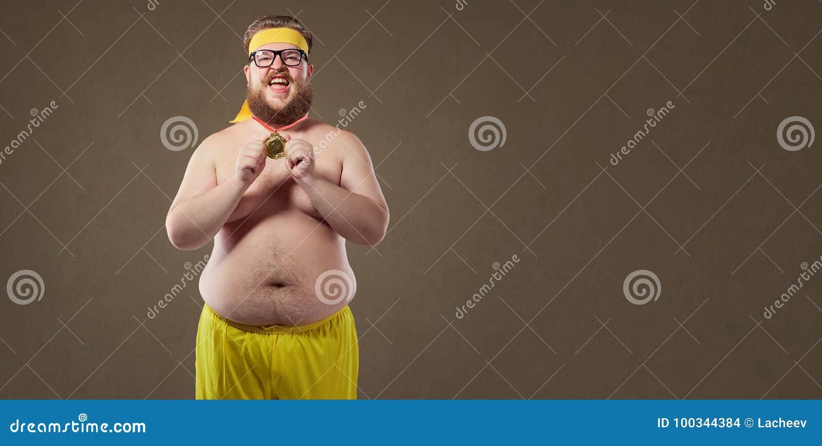 Dikke grappige mens met een medaille in zijn handen