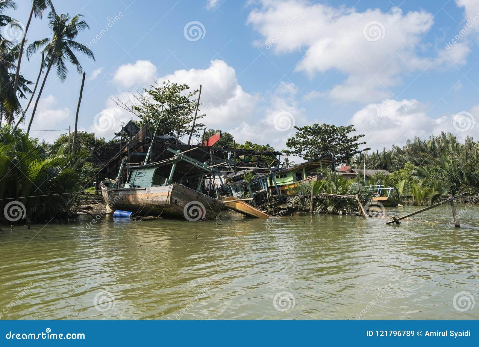 Dilapidated abandon fisherman boat stranded near the riverside a