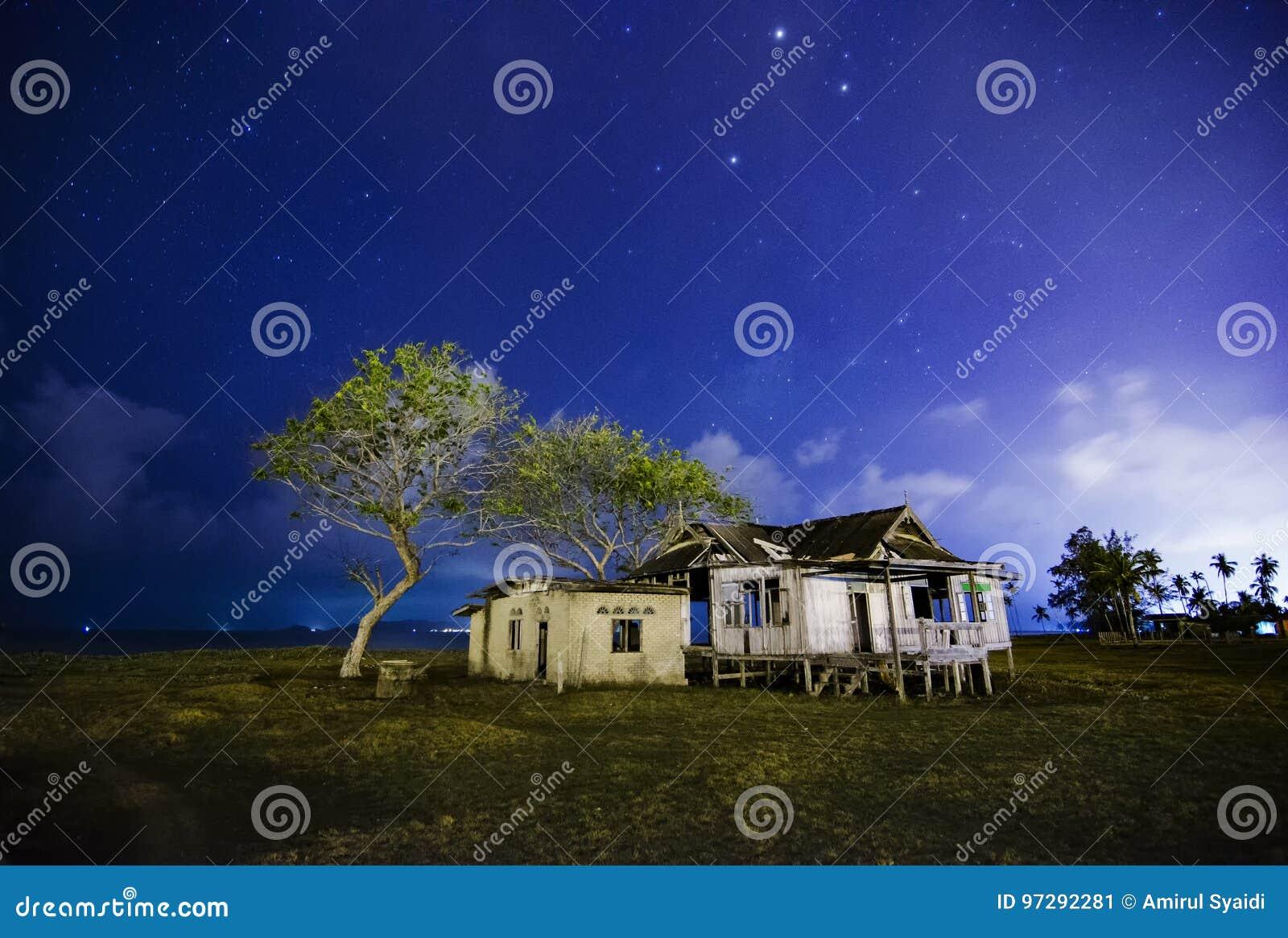 Dilapidated verlaat blokhuis bij nacht met ster en bewolkte hemelachtergrond