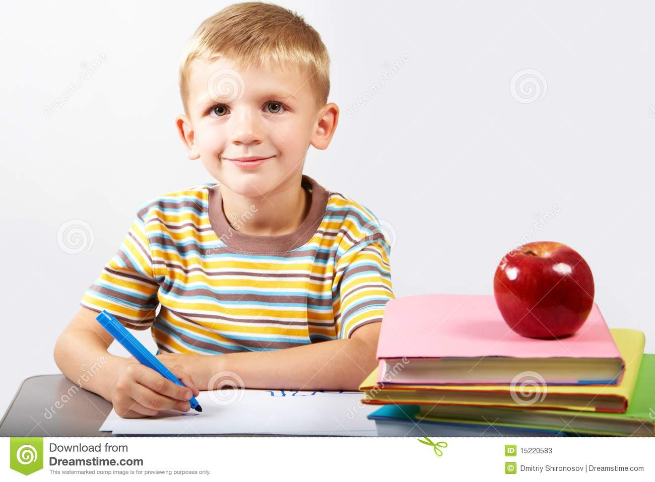 Diligent schoolboy looking at camera during drawing.