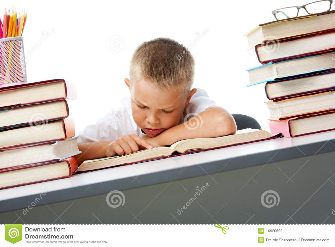 Smart youth reading open book before him with serious facial ...