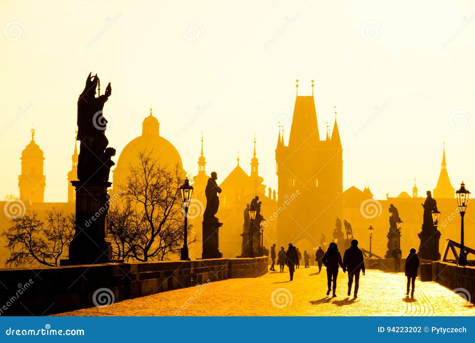 Dimmig morgon på Charles Bridge, Prague, Tjeckien Soluppgång med konturer av att gå folk, statyer och gammalt