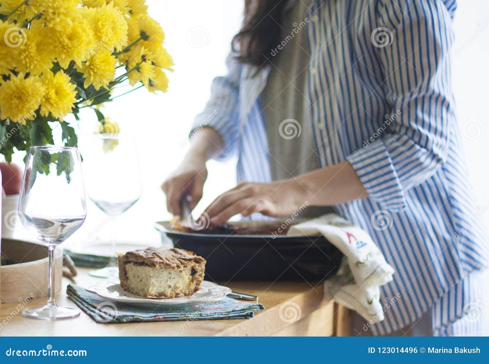 Diner voor de familie vrouw die gedeelten van voedsel geven Gediende lijst gele bloemen op de lijst lijst dichtbij het venster