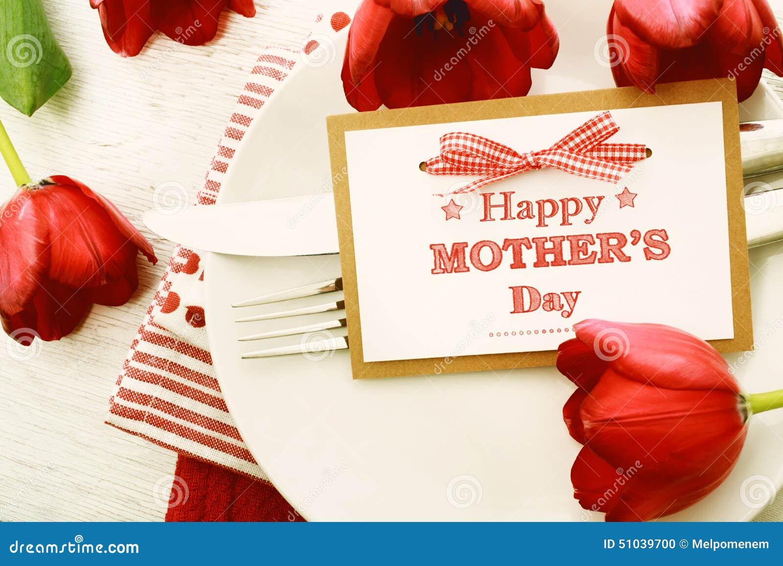 Dinerlijst die met het berichtkaart en tulpen van de Moedersdag plaatsen
