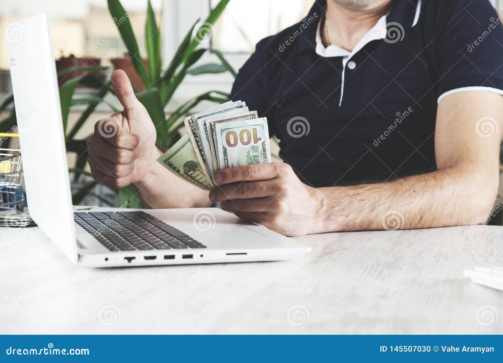 Dinero de mano del hombre con el teclado