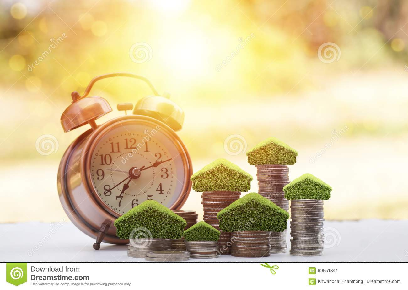 Dinero encendido apilado de monedas para ahorrar para la casa, el pequeño árbol y el hogar en pila con el despertador en la tabla