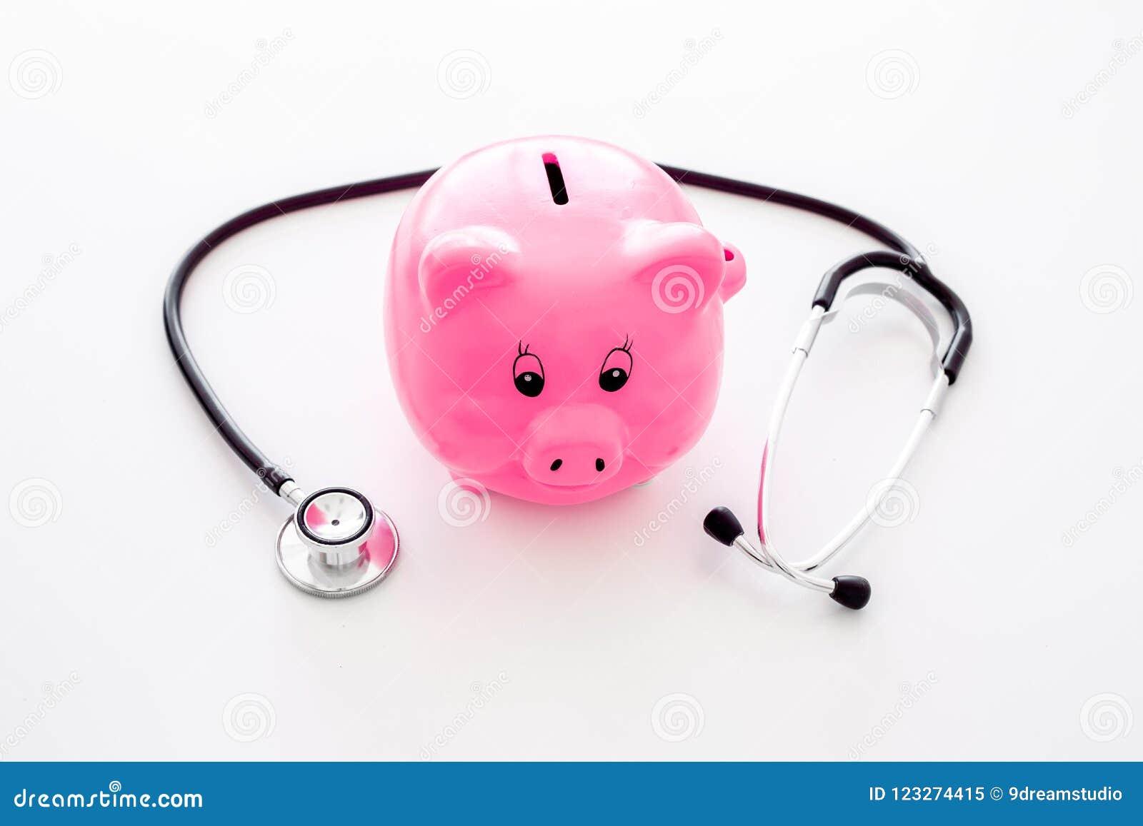 Dinero para el tratamiento Costos médicos Moneybox en la forma del cerdo cerca del estetoscopio en el fondo blanco