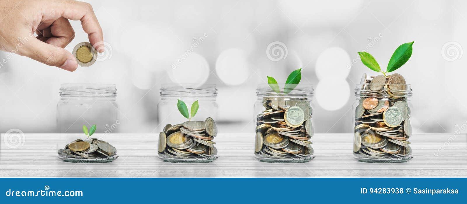 Dinheiro da economia e conceitos do investimento, mão que põe a moeda nas garrafas de vidro com incandescência das plantas