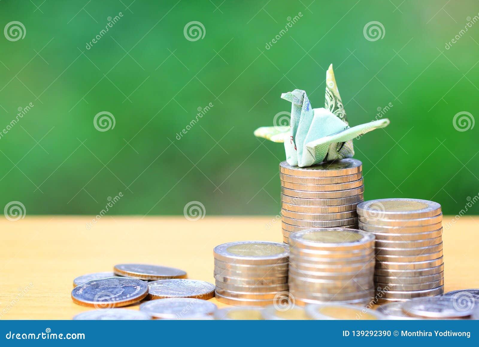 Dinheiro de salvamento, fazendo a um pássaro do origâmi a cédula tailandesa na pilha de dinheiro das moedas no fundo verde natura