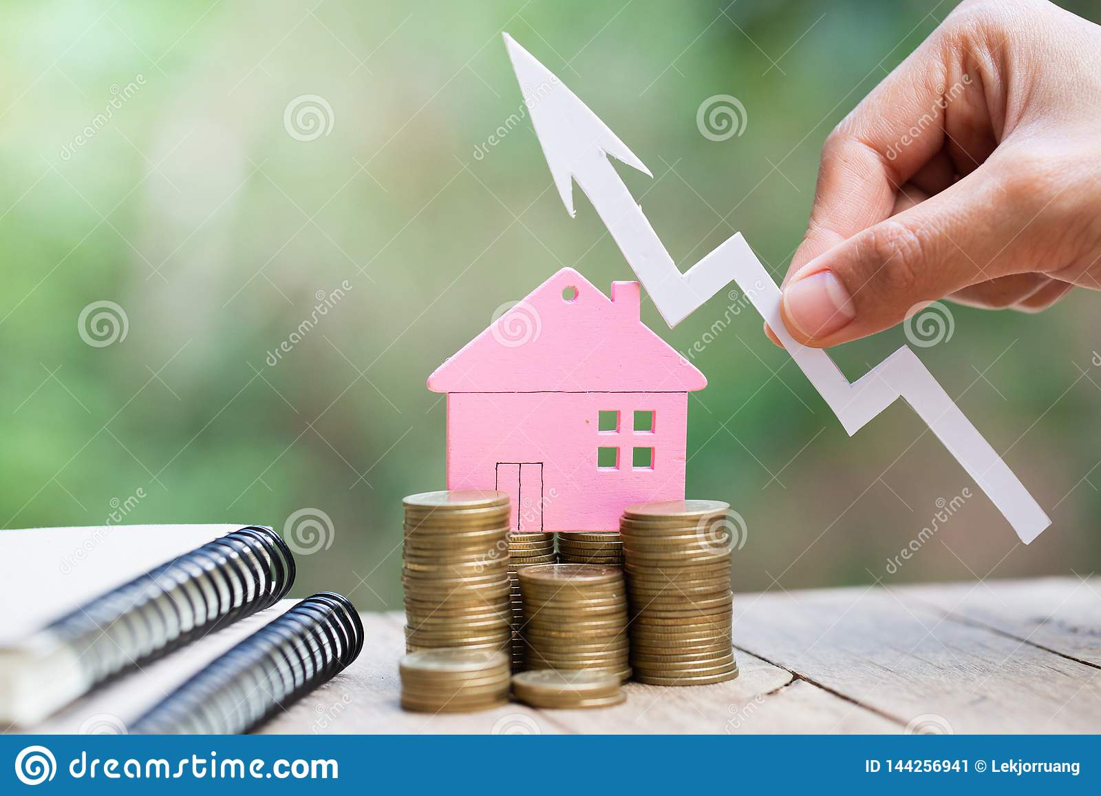 Dinheiro planejando das economias das moedas para comprar uma casa, o conceito para a escada da propriedade, a hipoteca e os orga