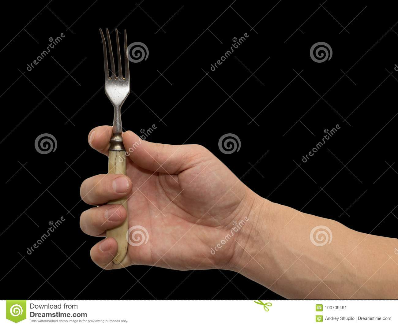 Dining fork in hand on a black background