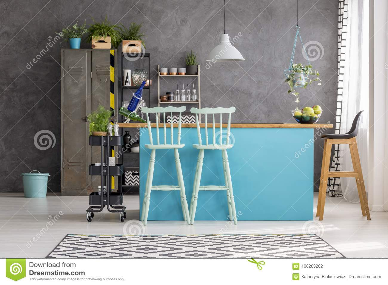 Wooden bar stools and blue dining table under lamp in room interior with grey wall metal locker and bin