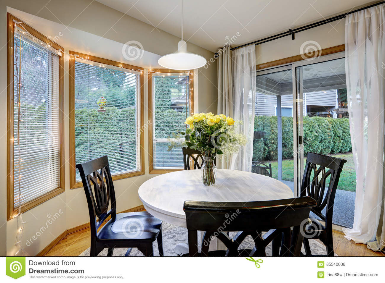 Dining Room With Curved Window Wall And Glass Sliding Doors Leading Out To Deck Yard Round White Washed Table Lined Black Chairs Topped