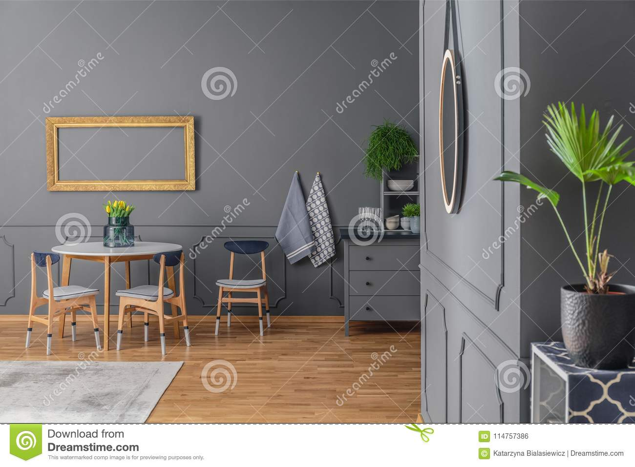 A Dining Room Interior With Grey Walls Wooden Floor Table Chairs And Gold Frame