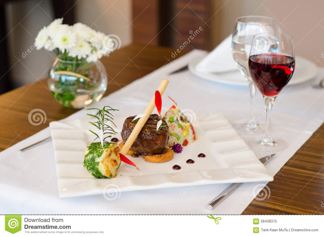 Dining table with steak and wine