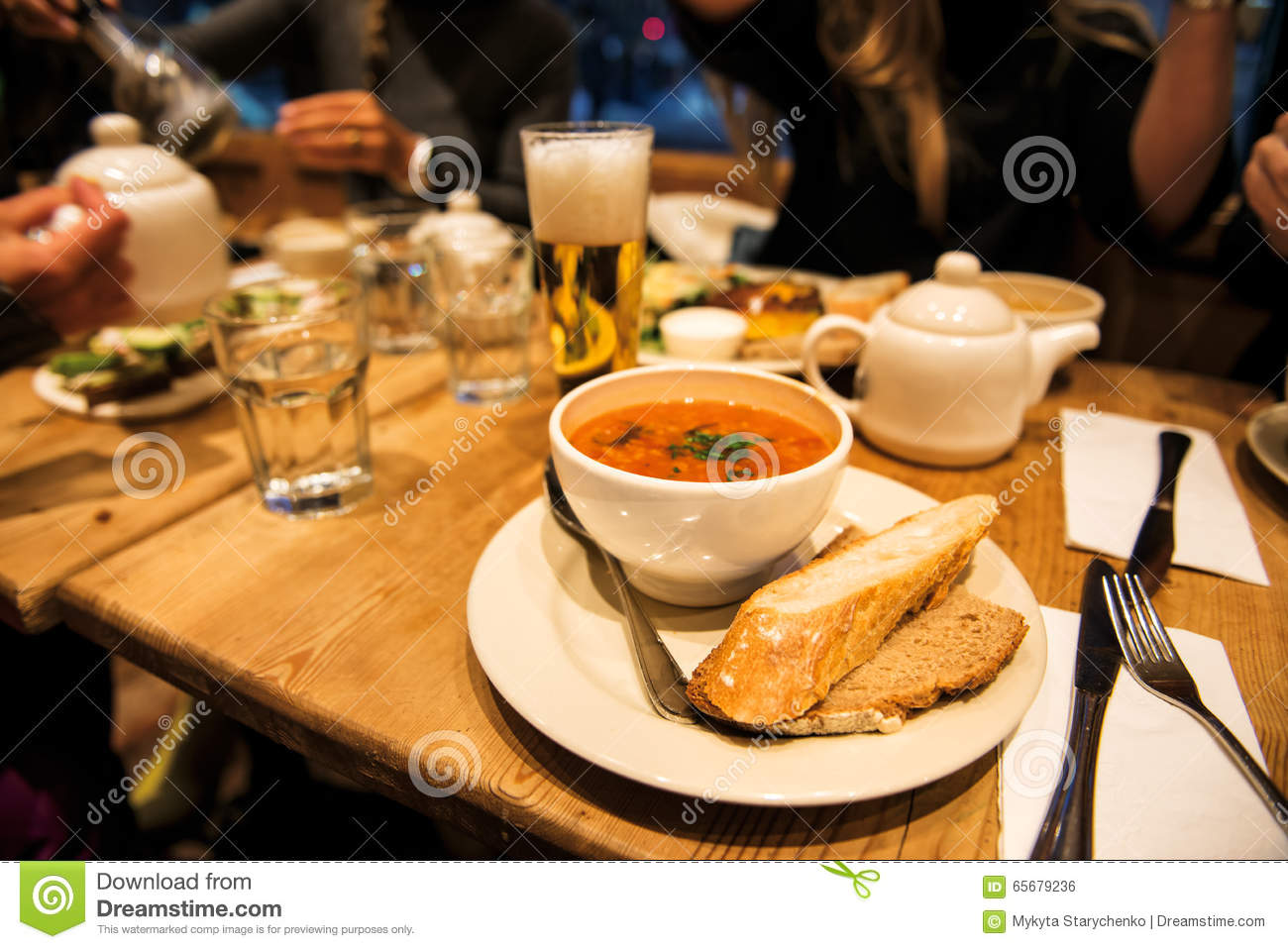 Dinner with friends in the restaurant with ministroni soup, bread, salad and beer