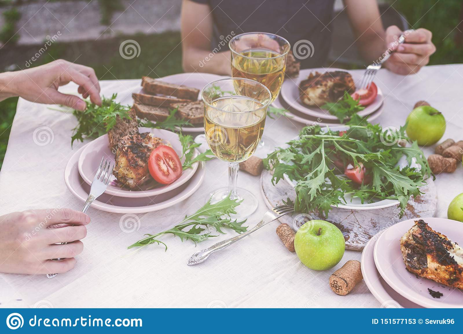 Dinner in the garden. People eat at the table with wine, grilled fish, fresh vegetables and herbs. Horizontal shot