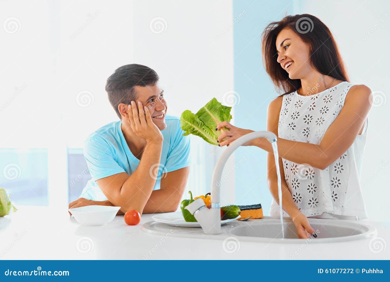 Dinner preparation. Loving couple washing vegetables.