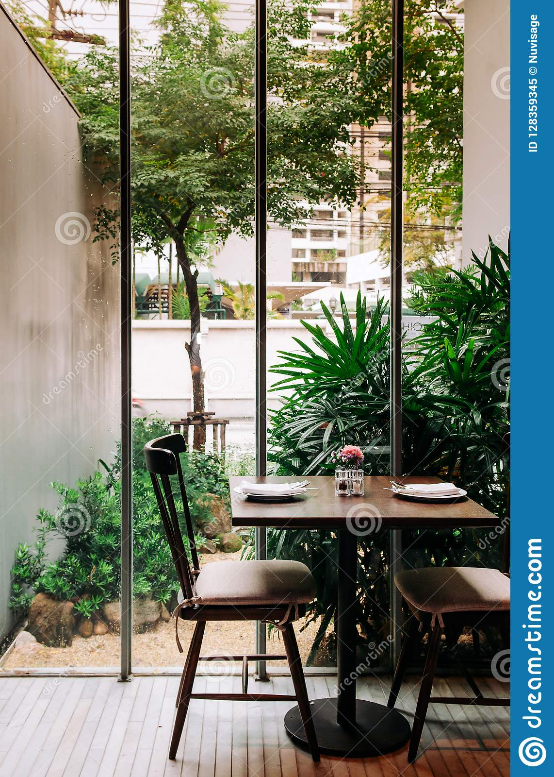 Superb OCT 17, 2013 Bangkok, Thailand   Contemporary Designed Wooden Dinner Table  In Modern Restaurant With Tropical Garden View Through Glass Wall