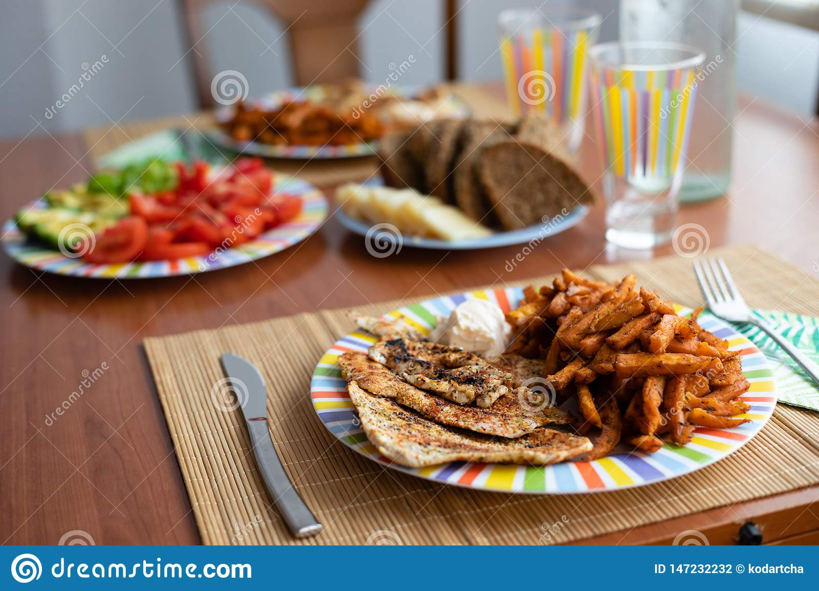 Dinner table with salad dish, chicken, sweet potatoes, bread and colorful water glass