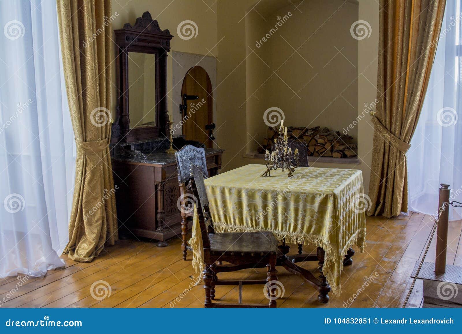 Dinning与桌,椅子,在古老老城堡的雕象的室内部