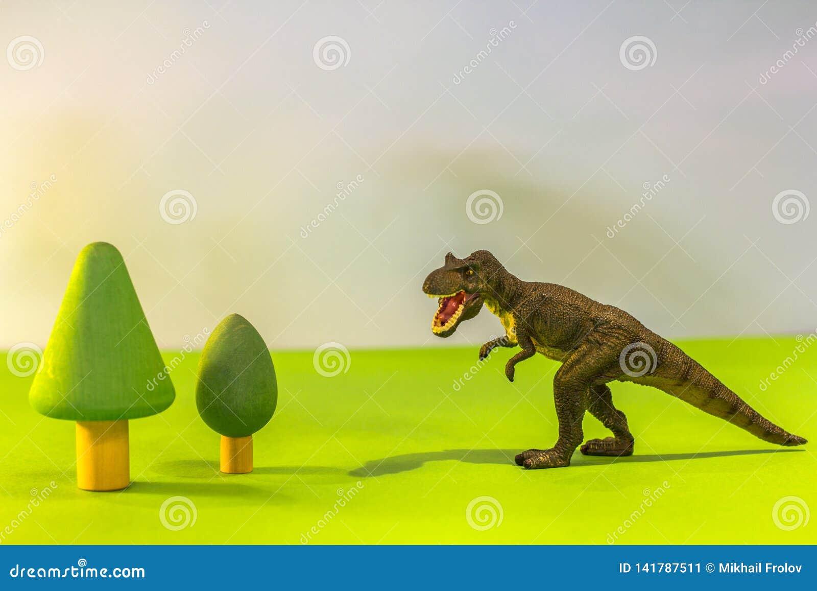 Dinosaure de jouet dans une forêt de jouet comme un vrai T-rex sur un fond lumineux de studio avec les arbres en bois Jouets d Ec
