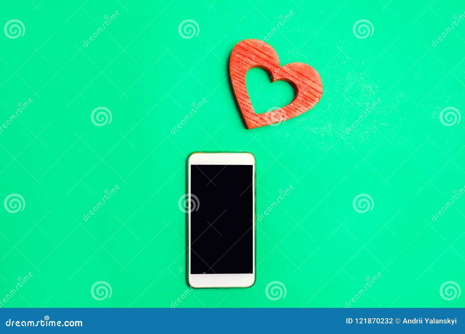 Dipendenza dalle reti sociali telefoni lo smartphone ed il cuore su un fondo verde datazione online, flirtare, messaggio e chiama