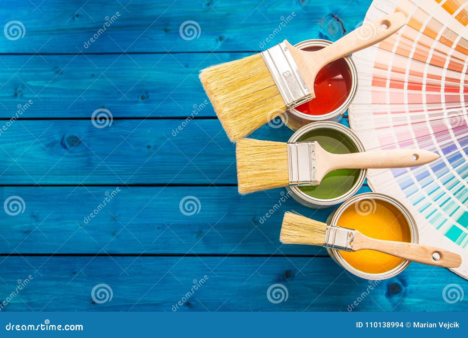 Dipinga la tavolozza di colore delle latte, latte aperte con le spazzole sulla tavola blu