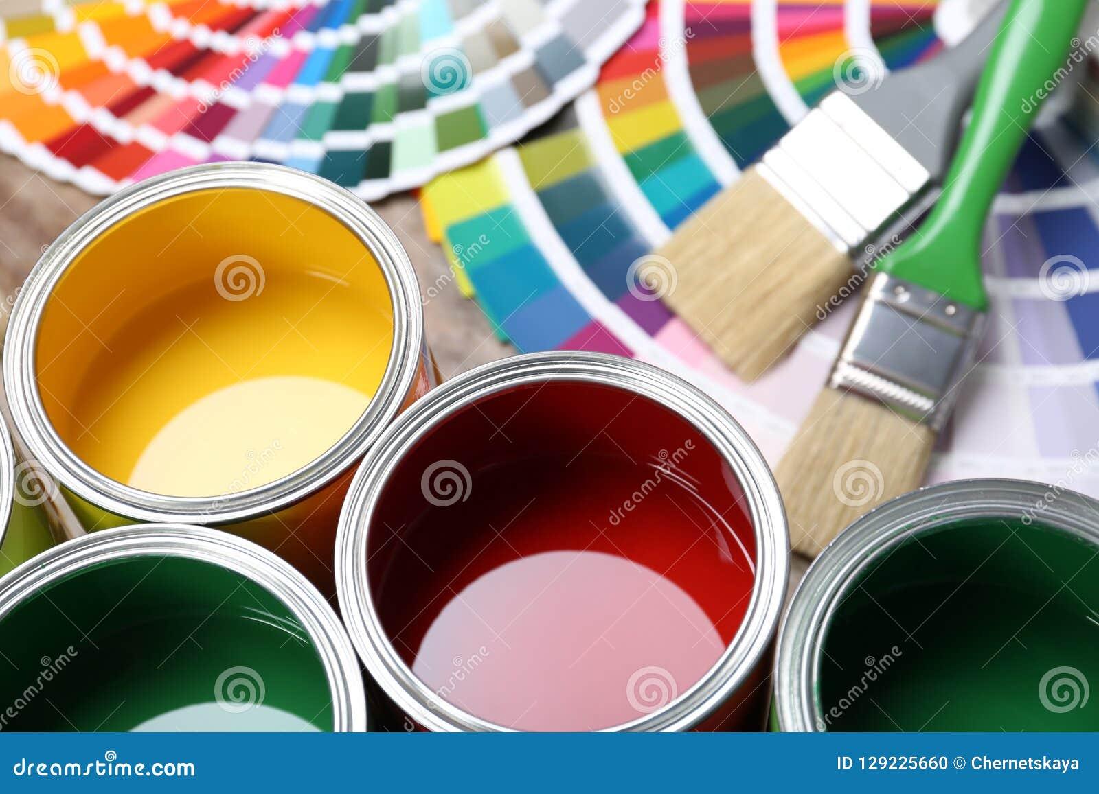 Dipinga le latte, i campioni della tavolozza di colore e le spazzole sulla tavola