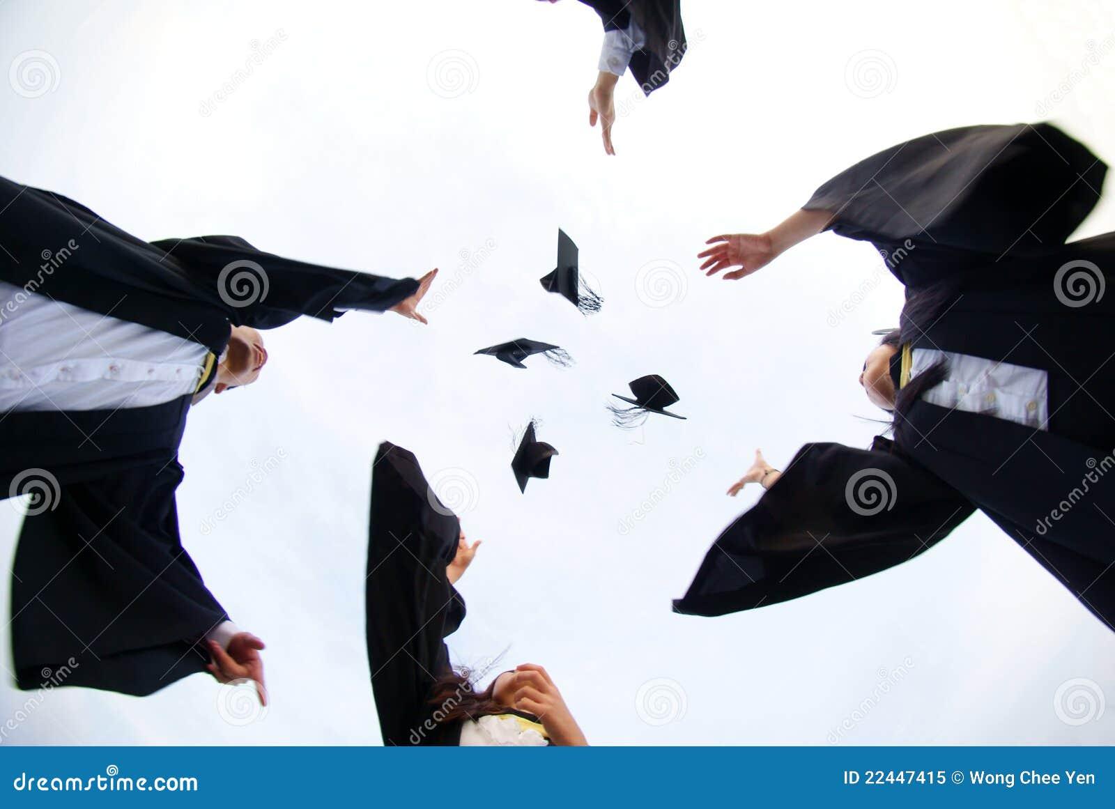 Diplômés heureux projetant des chapeaux