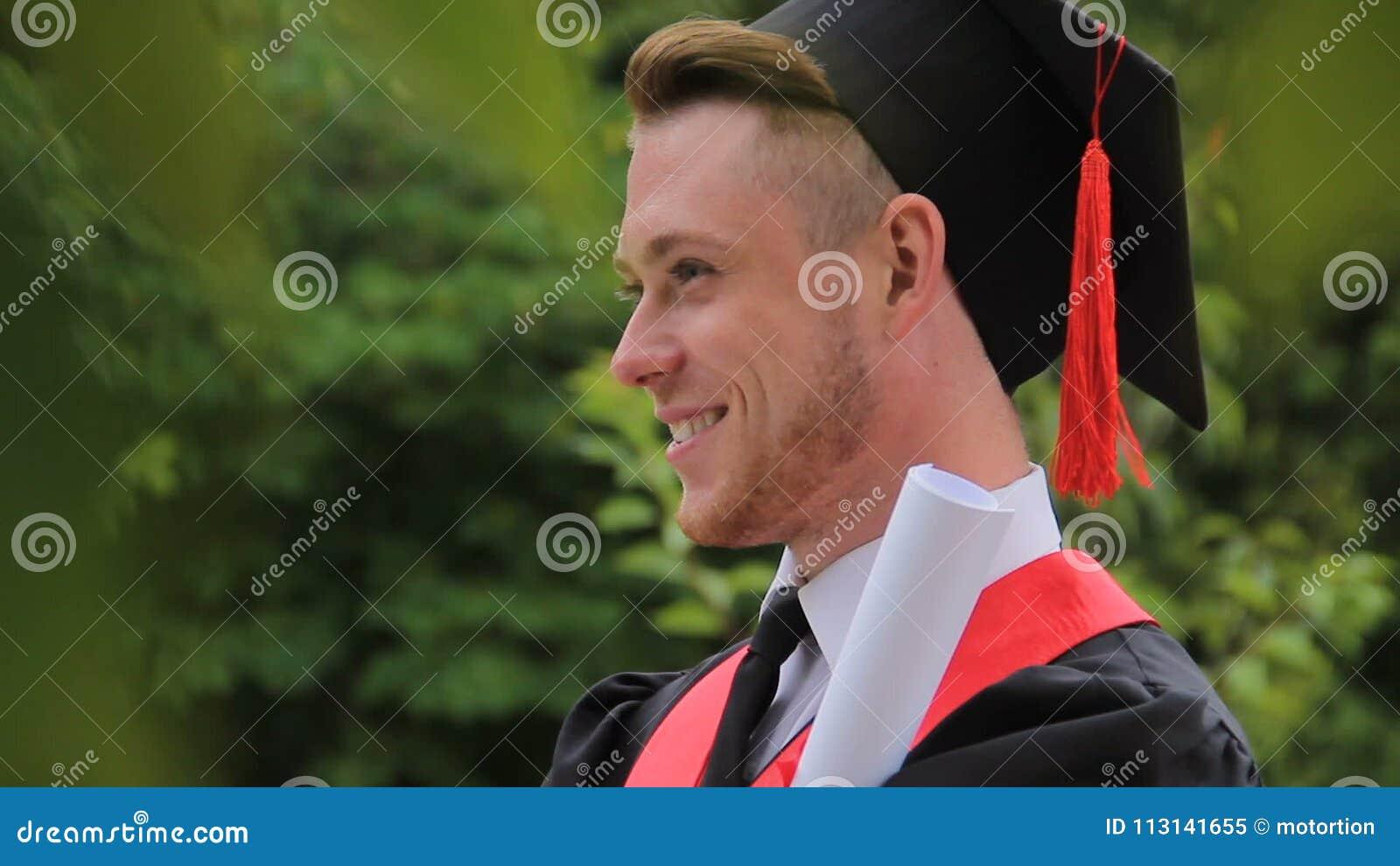 Diploma guardando graduado de sorriso satisfeito do homem e levantamento para a câmera, photoshoot filme