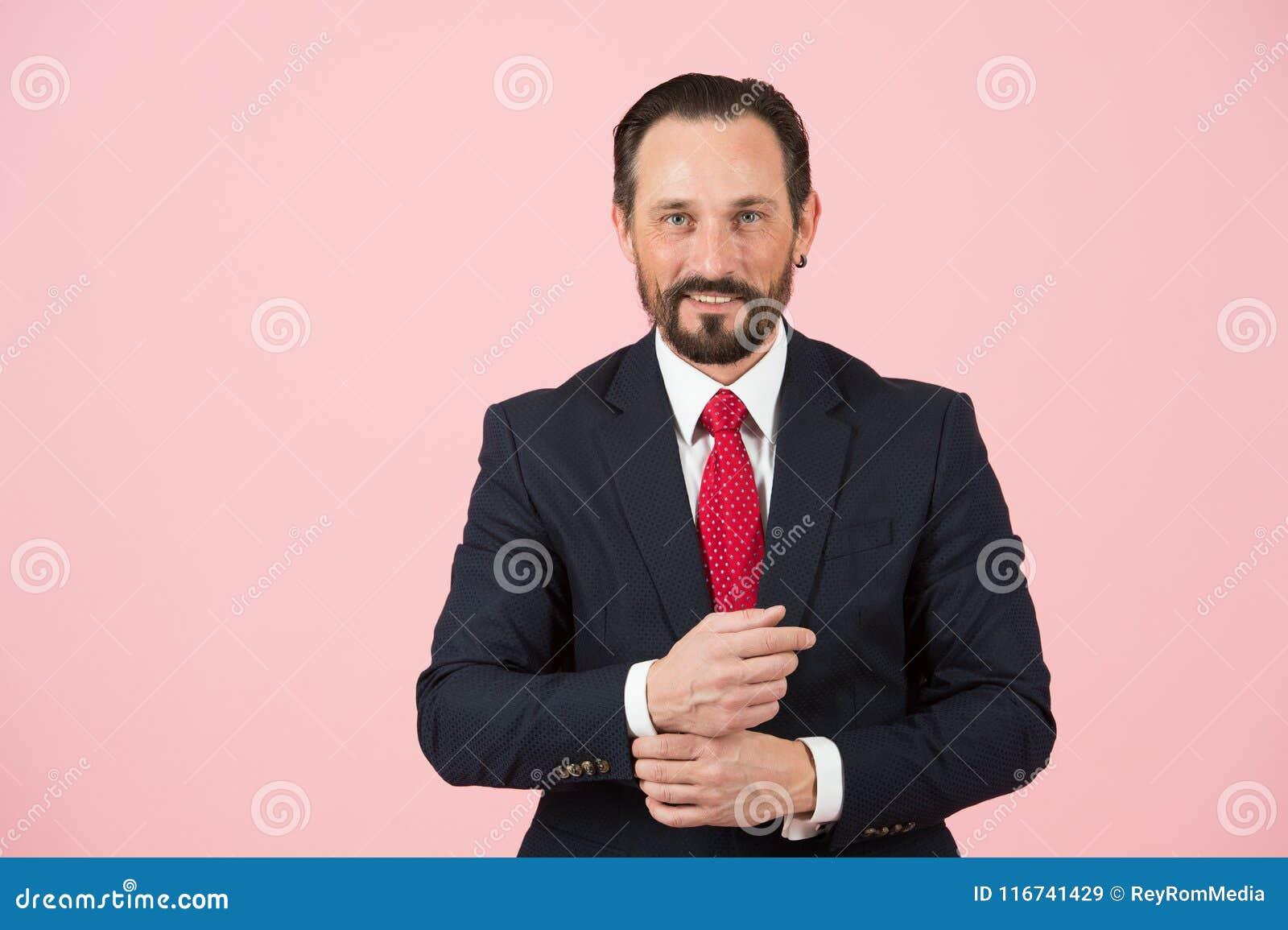 Directeur barbu dans le costume bleu d isolement sur le fond rose L homme d affaires âgé bel dans le costume noir regarde l appar