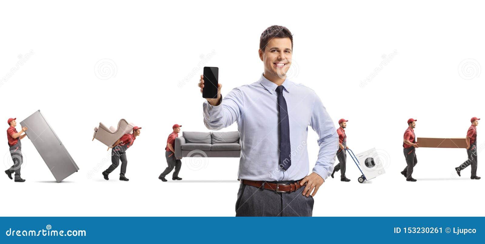 Directeur masculin avec un téléphone portable et des moteurs portant des meubles