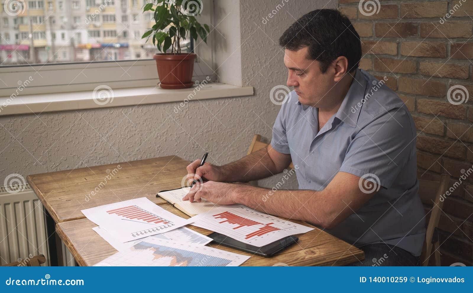 Directeur s asseyant au bureau, prenant des notes dans un carnet, sur les papiers dispersés par table