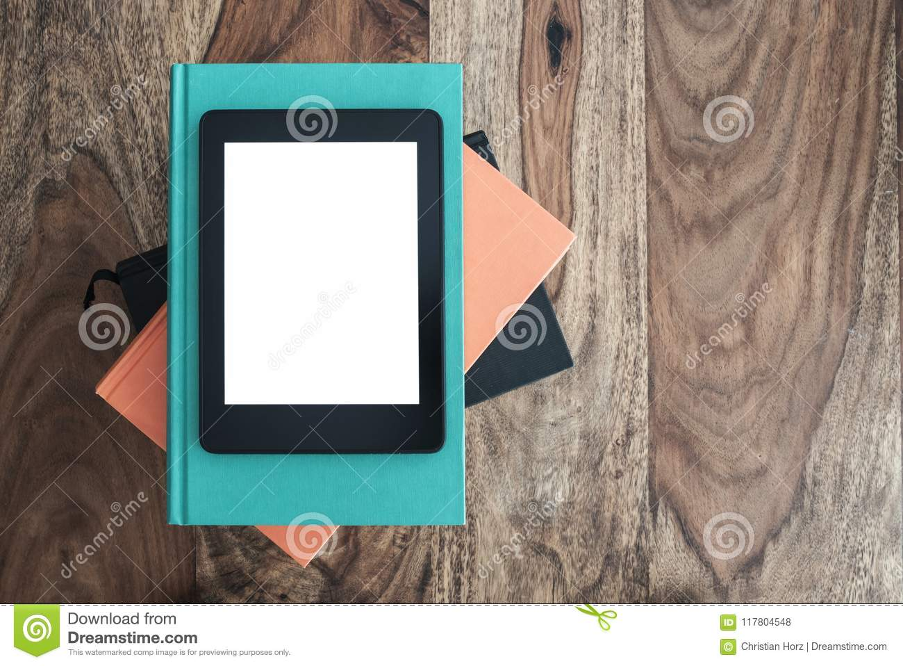 Top view of e-book reader on stack of books on wooden table