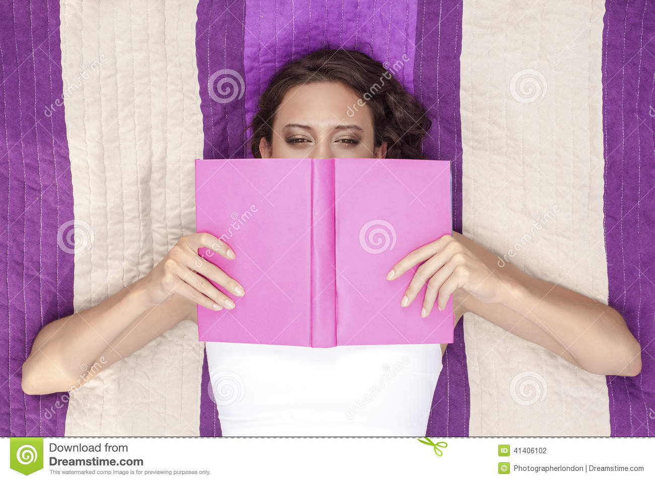Book Covering Face : Directly above shot of woman covering face with book while