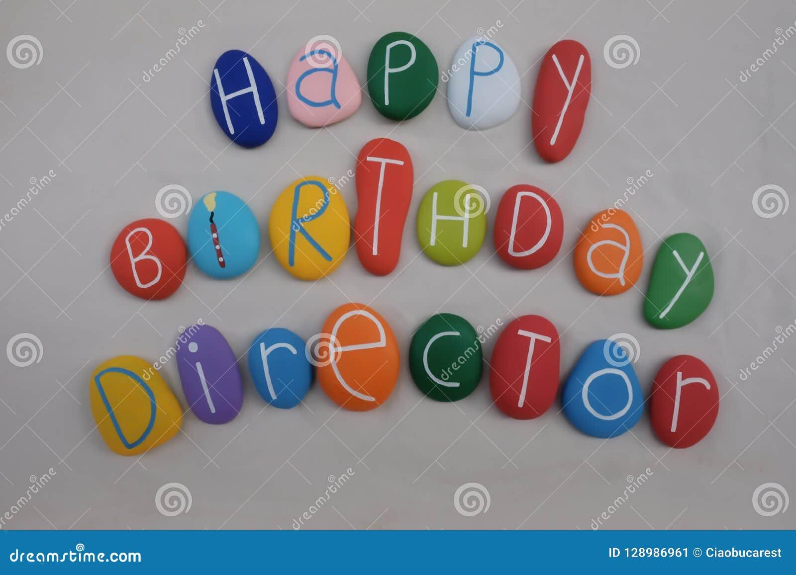 Director del feliz cumpleaños con las piedras coloreadas sobre la arena blanca