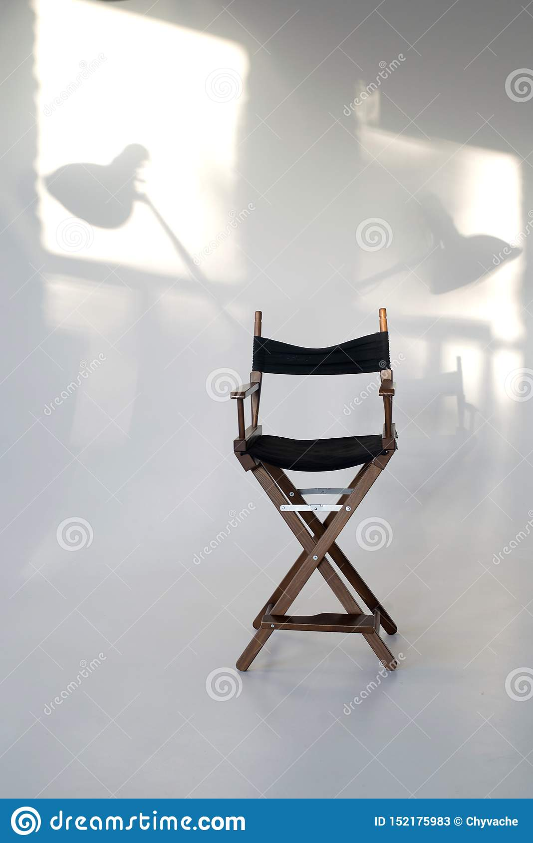 Director`s chair on a white background. shadows on the wall from the sun. light shades
